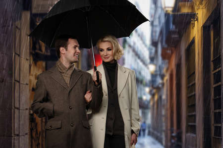 Elegant couple with umbrella walking outdoors in the rain photo