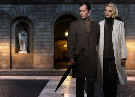house coats: Elegant couple in coats against building facade in evening