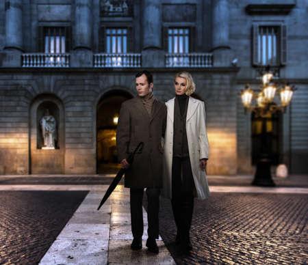 Elegant couple in coats against building facade in evening Stock Photo - 17507458