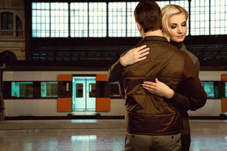 parting: Beautiful couple embracing on train station