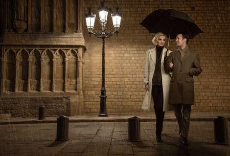 uomo sotto la pioggia: Coppia elegante con ombrello all'aperto in serata piovosa