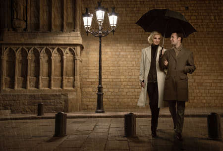Men and women in the rain: Vài thanh lịch với chiếc ô ngoài trời vào buổi tối mưa