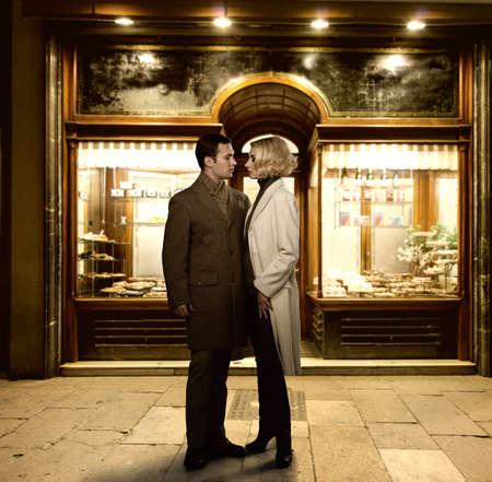Elegant couple against bakery shop window photo