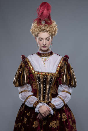 Haughty queen in royal dress isolated on grey photo