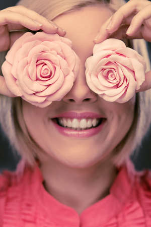 Happy blond woman with two rosebuds  photo