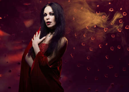 Beautiful vampire woman in red dress photo