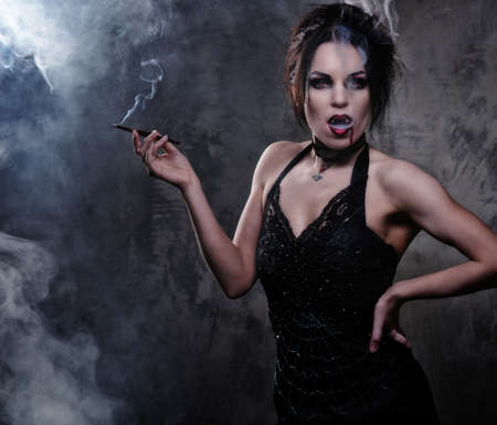 vampire: Beautiful vampire woman in black dress smoking Stock Photo