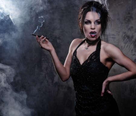 vampira sexy: Mujer vampiro hermosa en vestido negro de fumar