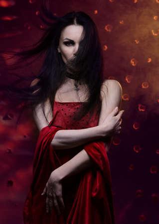 Beautiful vampire woman in red dress