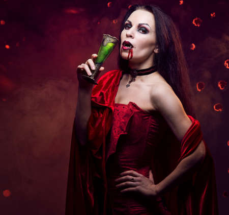 Beautiful vampire woman in red dress drinking photo
