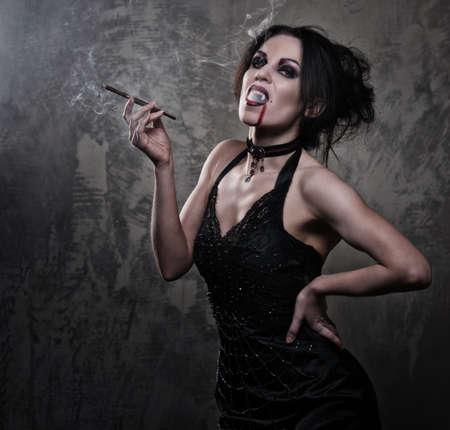 sexy halloween: Beautiful vampire woman in black dress smoking Stock Photo