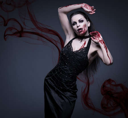 Beautiful vampire woman covered in blood photo