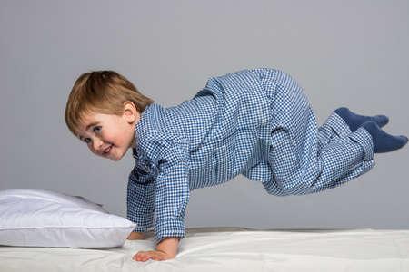 boy jumping: Ni�ito juguet�n pijama azul en la cama Foto de archivo