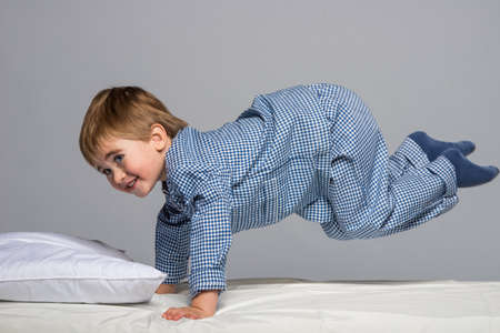 Playful little boy wearing blue pyjamas in bed photo