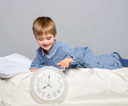 good time: Little boy in blue pyjamas with clock
