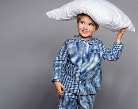 Little boy in blue pyjamas with pillow photo