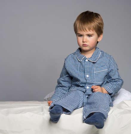 pijama: Decepcionado niño pequeño en pijama azul en la cama Foto de archivo