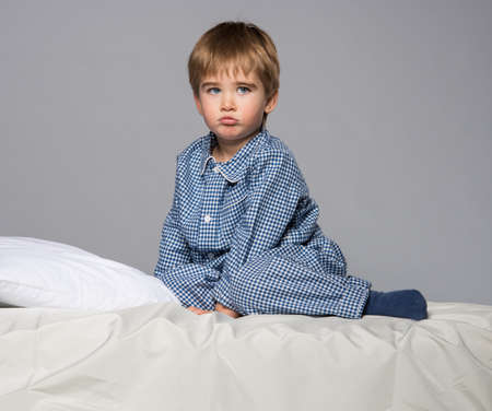 Disappointed little boy in blue pyjamas on bed photo