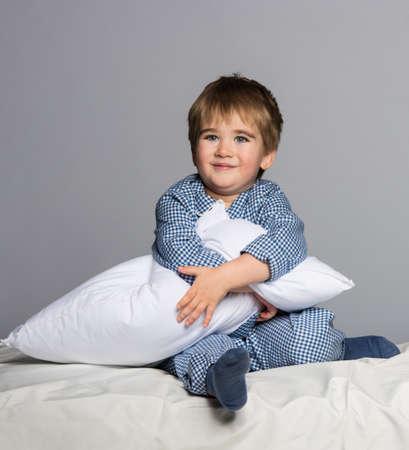 child in bed: Playful little boy wearing blue pyjamas in bed