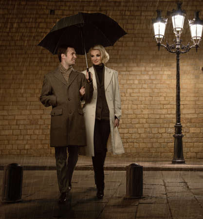 Elegant couple with umbrella outdoors on rainy evening photo