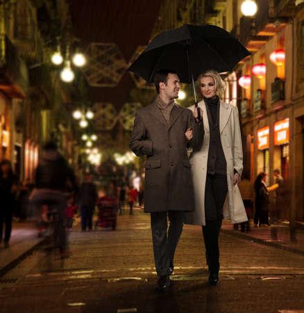 happy rich woman: Coppia elegante con ombrello all'aperto in serata piovosa