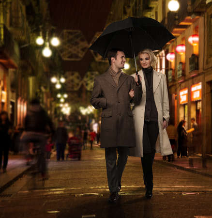 overcoat: Elegant couple with umbrella outdoors on rainy evening Stock Photo