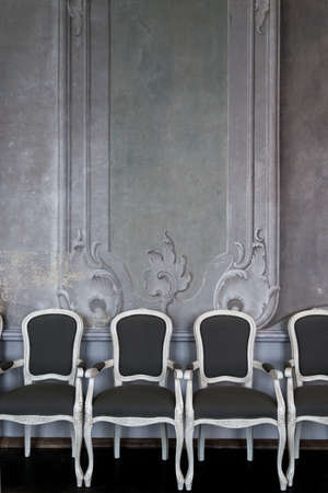 Comfortable chairs against luxury white wall design with mouldings photo