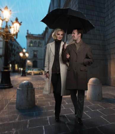 couple in rain: Elegant couple with umbrella outdoors on rainy evening Stock Photo