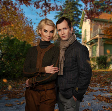 house coats: Elegant couple against country house on autumn day