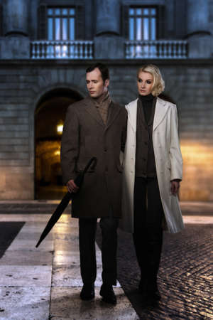 overcoat: Elegant couple in coats against building facade in evening
