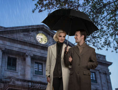 Elegant couple with umbrella against building facade  photo