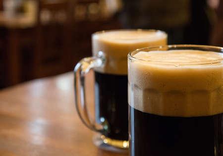 cerveza negra: Dos vasos de cerveza negra en la mesa Foto de archivo