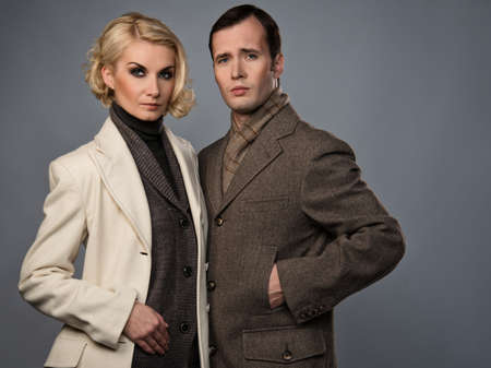overcoat: Elegant couple in coats isolated on grey