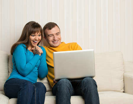inet: Happy couple sitting on sofa with laptop Stock Photo