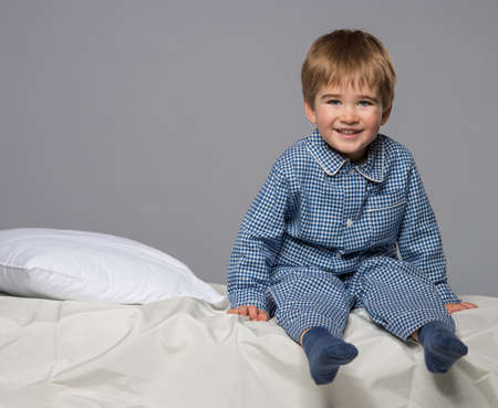 child in bed: Little boy wearing blue pyjamas in bed Stock Photo