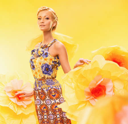 spring fashion: Beautiful young woman among big yellow flowers Stock Photo