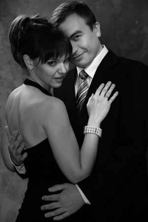 Monochrome picture of young man and woman in elegant evening dress photo