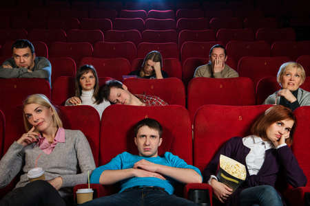 bored man: Group of boring people watching movie in cinema Stock Photo