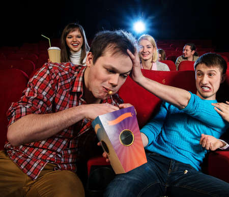 Impudent young man steal popcorn in cinema while people watching movie photo
