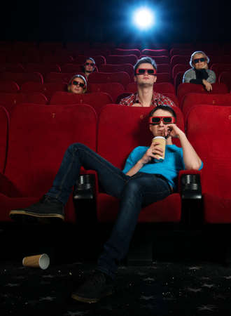 People in 3D glasses watching movie in cinema photo