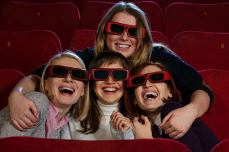 Group of excited young girls watching movie in cinema photo