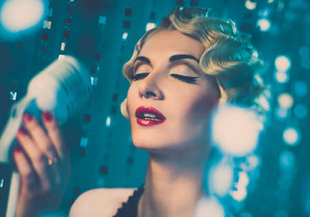 Elegant blond retro woman singer with beautiful hairdo and red lipstick photo