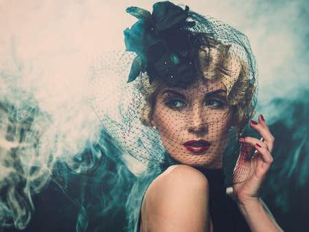 Elegant blond retro woman  wearing little hat with veil in smoke
