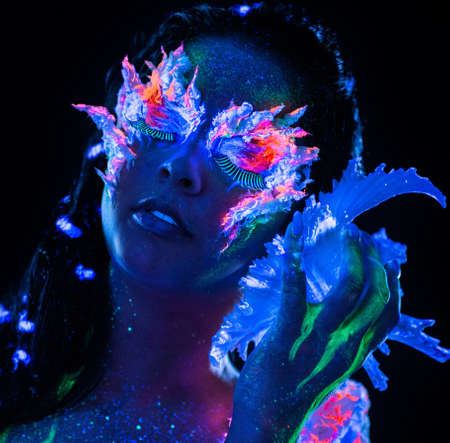 Portrait of beautiful woman with body art glowing in ultraviolet light photo