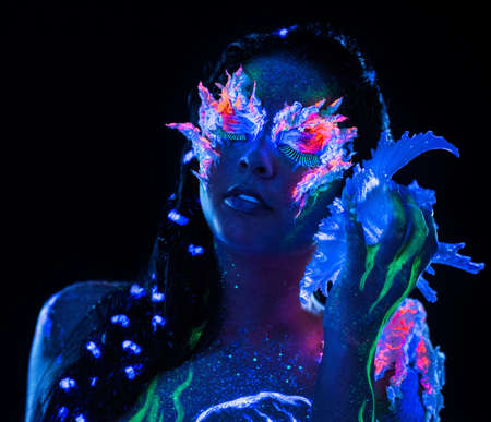 adult mermaid: Portrait of beautiful woman with body art glowing in ultraviolet light