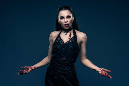 Beautiful vampire style woman in black dress with hands covered in blood photo