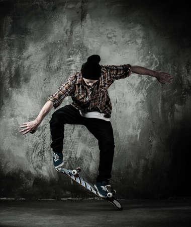 Jonge man in hoed en overhemd uitvoeren van stunt op skateboard Stockfoto