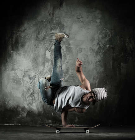 breakdance: Young b-boy man doing brake dancing movements on skateboard Stock Photo