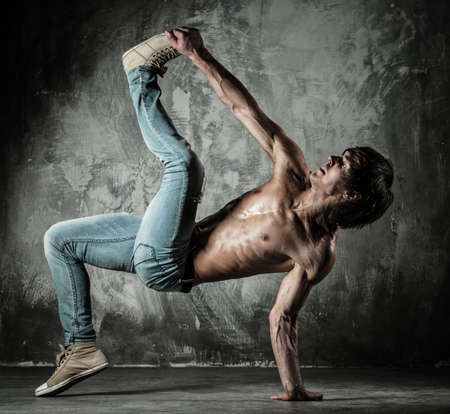 Young b-boy man with nude torso doing brake dancing movements  photo