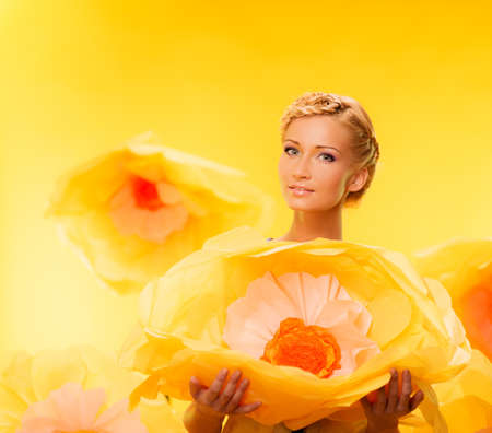 Beautiful young cheerful blond woman holding big yellow flower photo